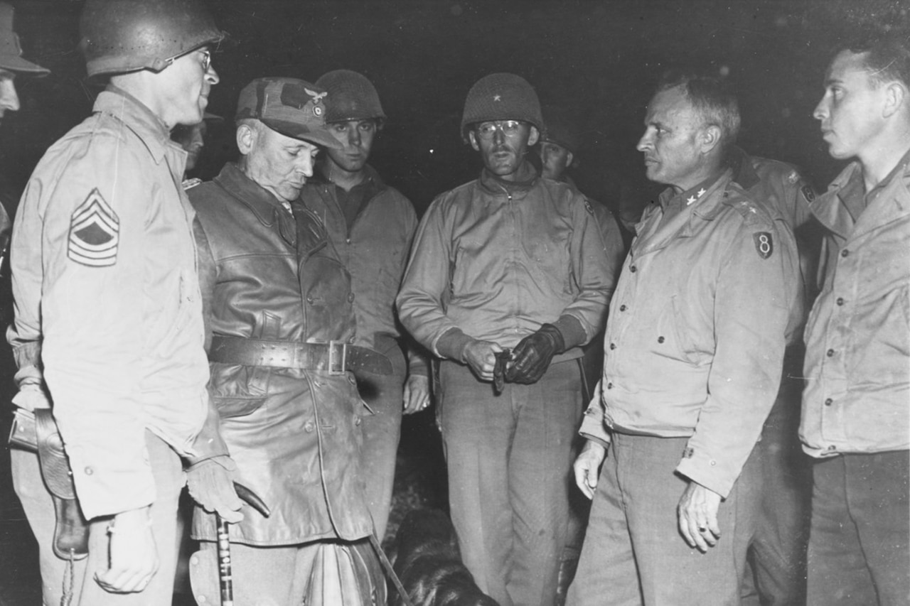 Several American soldiers wearing Army Eighth Division patches stand with a German general and his dog.