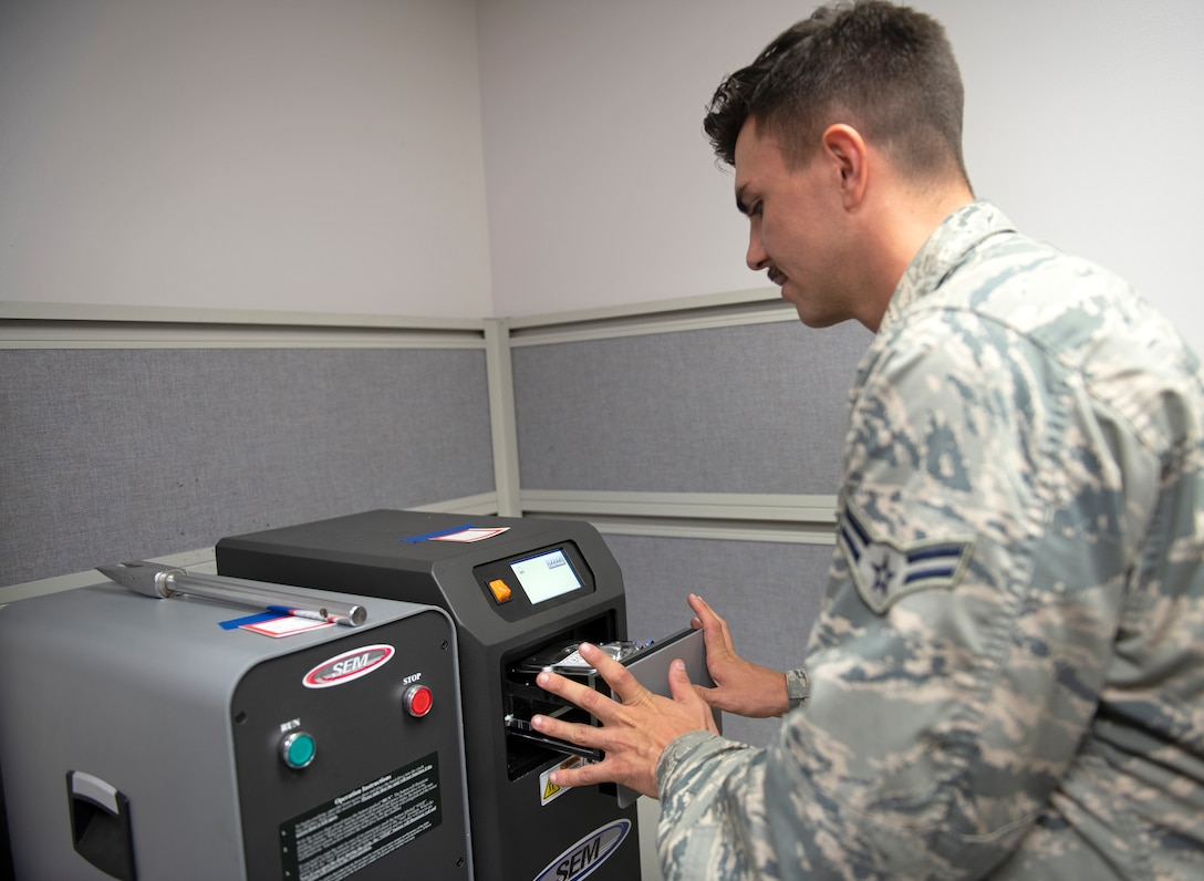 Airman 1st Class Stephen Lowe, 56th Communications Squadron cyber security technician, places a hard drive into a degausser July 31, 2019, at Luke Air Force Base, Ariz.