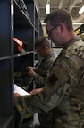 Senior Airmen Tyler and Jordan, 432nd Aircraft Maintenance Squadron support technicians, review a checklist at Creech Air Force Base, Nevada, July 29, 2019. Creech maintenance Airmen are trained to ensure tools are serviced and ready for use to complete the mission. (U.S. Air Force photo by Airman 1st Class William Rio Rosado)