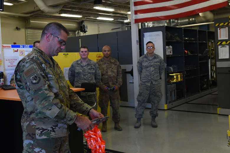 Col. Scott, 432nd Maintenance Group Commander, cuts the ribbon at the Tiger Aircraft Maintenance Unit at Creech Air Force Base, Nevada, July 29, 2019.  Prior to this grand opening, all Airmen were tasked with getting their tools from the Reaper Aircraft Maintenance Unit. (U.S. Air Force photo by Airman 1st Class William Rio Rosado)