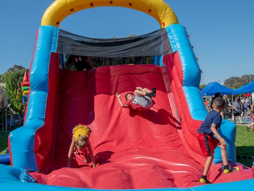 Children play on an inflatable slide during the 60th Security Forces Squadron National Night Out Aug. 6, 2019, at Travis Air Force Base, California. National Night Out is an annual community-building campaign that promotes police-community partnerships and neighborhood camaraderie. The event included a demonstration by military working dogs, live music and a variety of activities for children. (U.S. Air Force photo by Heide Couch)