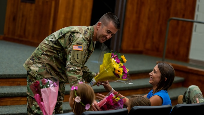 Chief Warrant Officer 4 Ryan Little,  of Pleasant Plains, Illinois, presents flowers to wife Jade, and daughters Molly and Kate, during his promotion ceremony at Camp Lincoln, Springfield, Illinois, August 7, 2019. Chief Warrant Officer 4 Little serves as the Senior Maintenance Officer, Joint Force Headquarters, Illinois National Guard.
