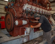 Machinist, Michael Buehler, wrenches on a massive, 8-foot tall Paxman engine in the Engine Shop, at Production Plant Barstow, Marine Depot Maintenance Command, on the Yermo Annex aboard Marine Corps Logistics Base Barstow, Calif., July 30.