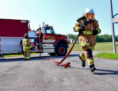 A cadet runs with a fire hose during a demonstration on the last day of the Fire Explorer Program on Joint Base Andrews, Md., July 27, 2019. Each cadet was challenged to perform search and rescue procedures, CPR, operate a fire hose, and put out a controlled fire in a timely manner.
