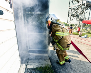A cadet runs into a smoke filled building to demonstrate his proficiency in the search and rescue skills taught during the Fire Explorer Program on Joint Base Andrews, Md., July 27, 2019. During this challenge, cadets were expected to navigate a smoke-filled building to find a hidden manikin and return it to safety.
