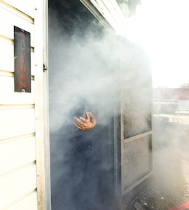 Corey Garritsen, 11th Civil Engineer Squadron Fire Department inspector, reaches a hand out to invite others to watch the cadets navigate a smoke filled room on Joint Base Andrews, Md., July 27, 2019. Smoke machines filled the rooms making it hard to see without proper gear.