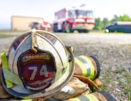 An 11th Civil Engineer Squadron fire safety helmet is left on the ground while 11th CES firefighters assist cadets during the Fire Explorer Program on Joint Base Andrews, Md., July 27, 2019. Members of the JBA fire department have been orchestrating the FEP for over three years.