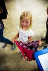 Jaidyn Wright, daughter of Staff Sgt. Steven Wright and his wife Leah, displays her belief in Unicorns and the Back To School Brigade's school supply giveaway at the annual event held at the Maj. Gen. James L. Day Conference Center aboard Marine Corps Logistics Base Barstow, California, Aug. 1.