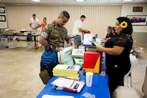 First Sergeant Enrique De Anda, MCLB Barstow HQ Co first sergeant, picks up school supplies for the young students in his extended family from volunteer Janet Rocha-Diaz at the Back To School Brigade annual school supply giveaway, Aug. 1, at the Maj. Gen. James L. Day Conference Center aboard the base.