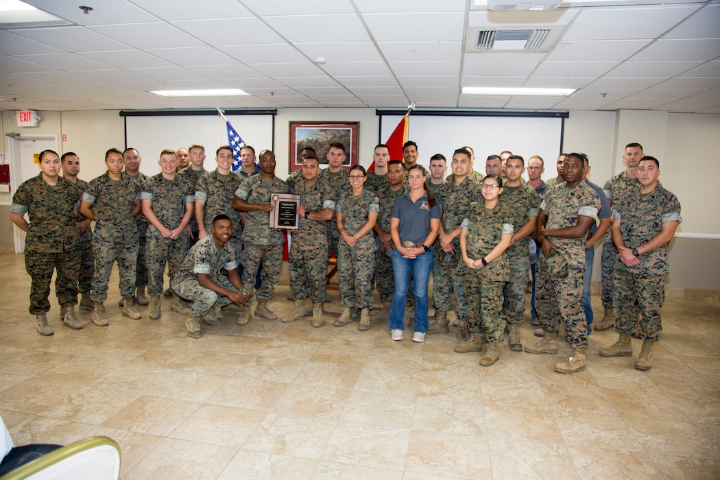 Members of Headquarters Company, Marine Corps Logistics Base Barstow, Calif., gather around company commander Maj. Ernest Robinson as he displays the plaque detailing the Voluntary Protection Program's Installation Safety Achievement Award. The plaque was presented to all departments aboard base for their part in making possible the award for installation safety and the Individual Safety Achievement award for a Special Government Employee. The plaque was presented during the Quarterly Awards breakfast held at the Maj. Gen. James l. Day Conference Center aboard base Aug. 6.