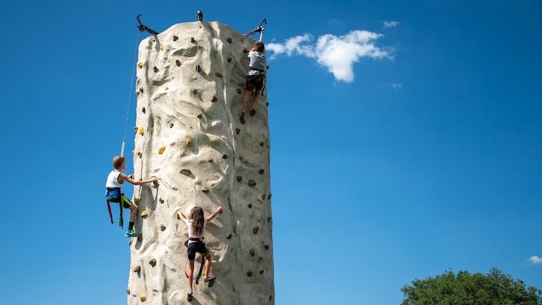 Children ascend a climbing wall during the annual Salute Picnic at Hill Air Force Base, Utah, Aug. 2, 2019. This was the 19th year the Top of Utah Military Affairs Committee sponsored the event for Hill's military and family members. The first event was held December 2001 as a welcome home celebration for military deployed following 9/11. (U.S. Air Force photo by R. Nial Bradshaw)