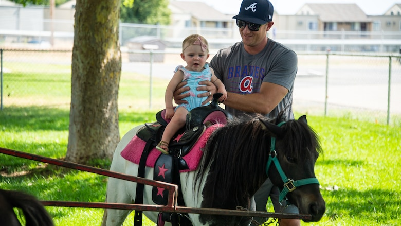 Josie rides a pony carousel with her father John Hazel during the annual Salute Picnic at Hill Air Force Base, Utah, Aug. 2, 2019. This was the 19th year the Top of Utah Military Affairs Committee  sponsored the event for Hill's military and family members. The first event was held December 2001 as a welcome home celebration for military deployed following 9/11. (U.S. Air Force photo by R. Nial Bradshaw)