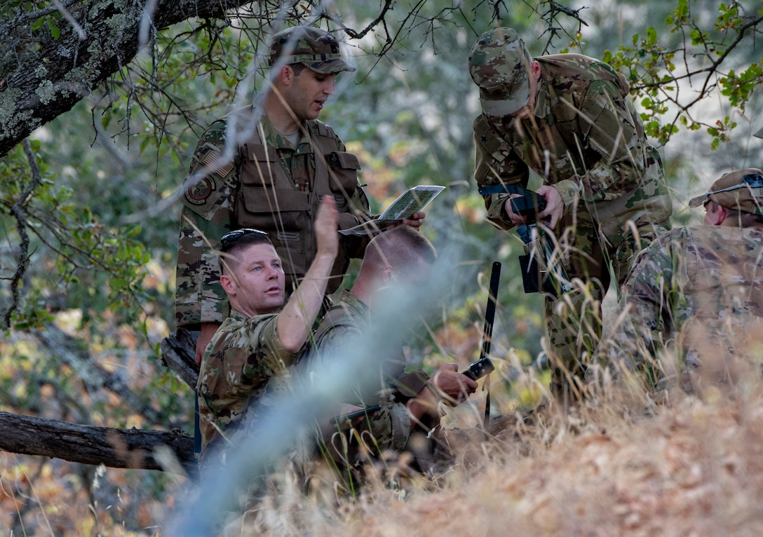 Aircrew members use communication devices and other supplies during a Survival, Evasion, Resistance and Escape training exercise that will last well into the evening, Aug. 5, 2019 in a remote area near Travis Air Force Base, California. SERE instructors conduct the training to improve aircrew's skill sets and update them on new techniques, procedures and technologies. (U.S. Air Force photo by Heide Couch)