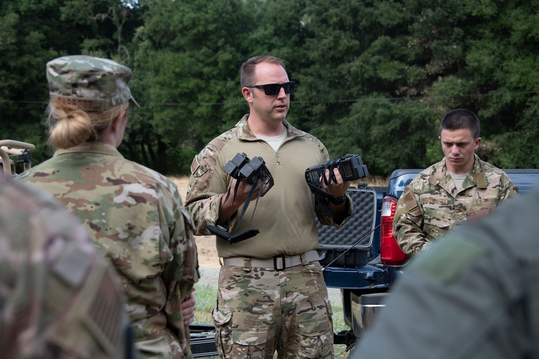 U.S. Air Force Tech. Sgt. Benjamin Heard, 60th Operations Squadron survival, evasion, resistance and escape training NCO officer in charge gives last minute instruction on communication devices before a SERE training exercise for aircrew members that will last well into the evening, Aug. 5, 2019 in a remote area near Travis Air Force Base, California. SERE instructors conduct the training to improve aircrew's skill sets and update them on new techniques, procedures and technologies. (U.S. Air Force photo by Heide Couch)