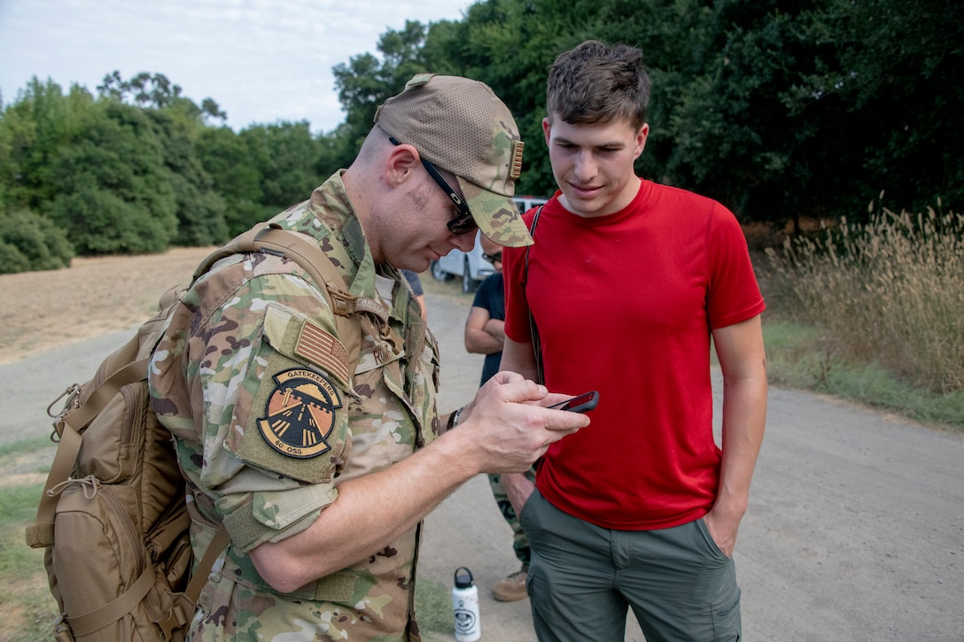 U.S. Air Force Tech. Sgt. Bernie Rowe, 60th Operations Support KC-10 Extender instructor flight engineer, and Nate Simon, Somewear Labs product manager, review procedures for new communications technology during a Survival, Evasion, Resistance and Escape Aug. 5, 2019, near Travis Air Force Base, California. Trainees followed SERE instructors point-to-point to learn the process of gathering materials, seeking shelter, discarding unnecessary supplies, finding food and testing improved communication equipment. (U.S. Air Force photo by Heide Couch)
