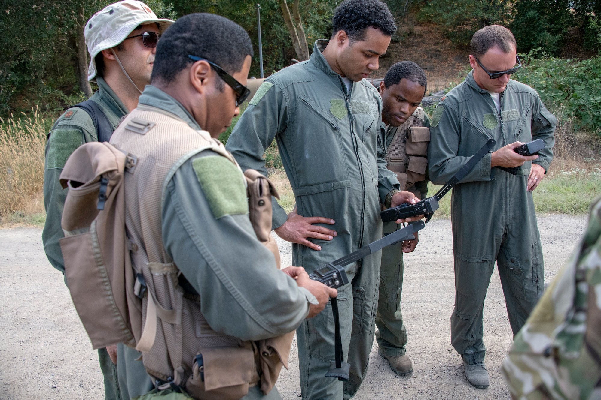 U.S. Air Force aircrew members study communication devices utilized during a Survival, Evasion, Resistance and Escape training exercise that will last well into the evening, Aug. 5, 2019, in a remote area near Travis Air Force Base, California. SERE instructors conduct the training to improve aircrew's skill sets and update them on new techniques, procedures and technologies. (U.S. Air Force photo by Heide Couch
