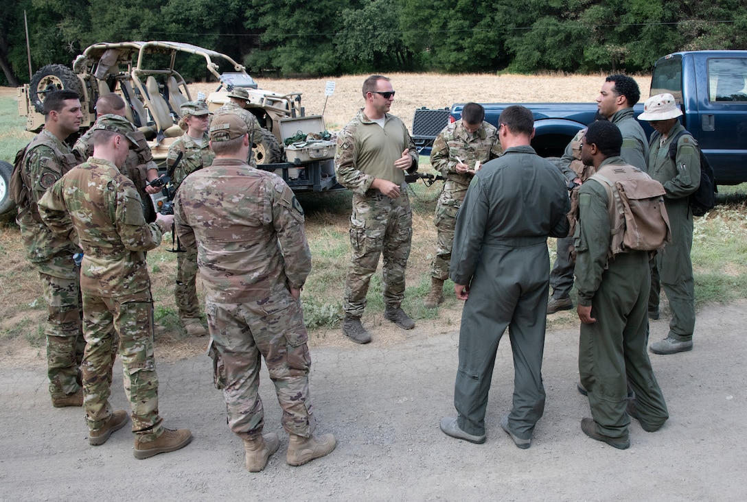 U.S. Air Force Tech. Sgt. Benjamin Heard, center, 60th Operations Squadron Survival, Evasion, Resistance and Escape training noncommissioned officer in charge gives last minute instruction on communication devices before a SERE training exercise for aircrew members, Aug. 5, 2019 in a remote area near Travis Air Force Base, California. SERE instructors conduct the training to improve aircrew's skill sets and update them on new techniques, procedures and technologies. (U.S. Air Force photo by Heide Couch)