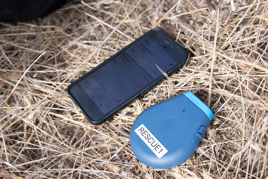 U.S. Air Force Survival, Evasion, Resistance and Escape personnel field test a developmental device Somewear Lab's Hotspot Aug. 5, 2019, in a remote area near Travis Air Force Base, California. Paired with a combat-configured smartphone, the system supports digital maps for navigation, modern digital satellite messaging and data transmission, and comprehensive blue-force tracking for the tactical operations center or any command. This device is one of the lightest and smallest of its kind and a major enhancement from the current survival kit.