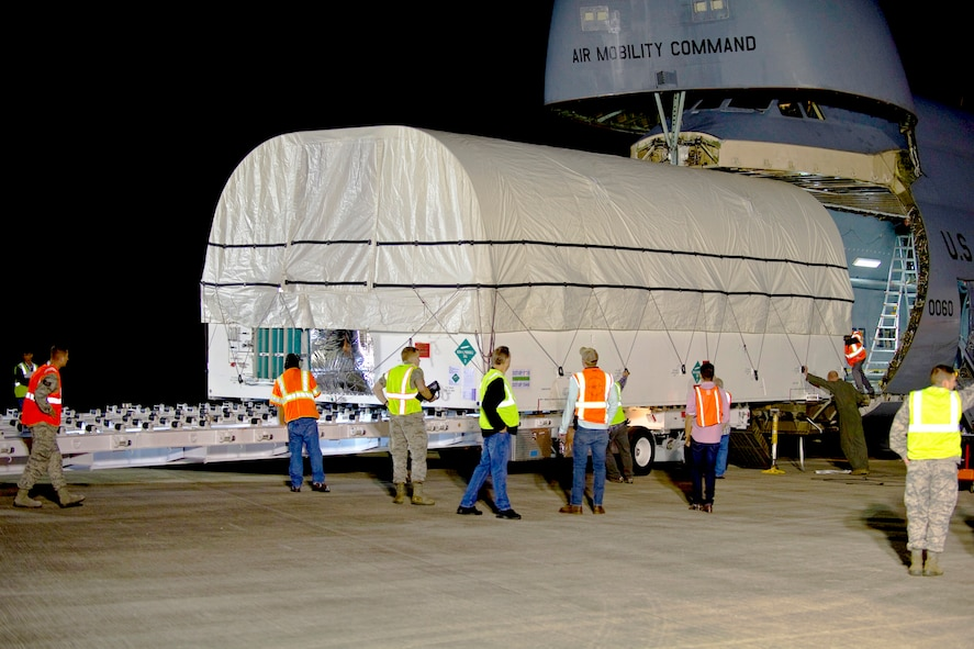 The air crew from the C-5C Galaxy, 22nd Airlift Squadron, from Travis Air Force Base, Calif., members of the Space and Missile Systems Center, the 45th Space Wing, and civilian ground crews, unload the fifth Advanced Extremely High Frequency (AEHF-5) communications satellite, at Cape Canaveral, Fla., April 22, 2019. The AEHF constellation is designed to replace the Milstar satellite constellation. (U.S. Air Force photo by Ian Bush)