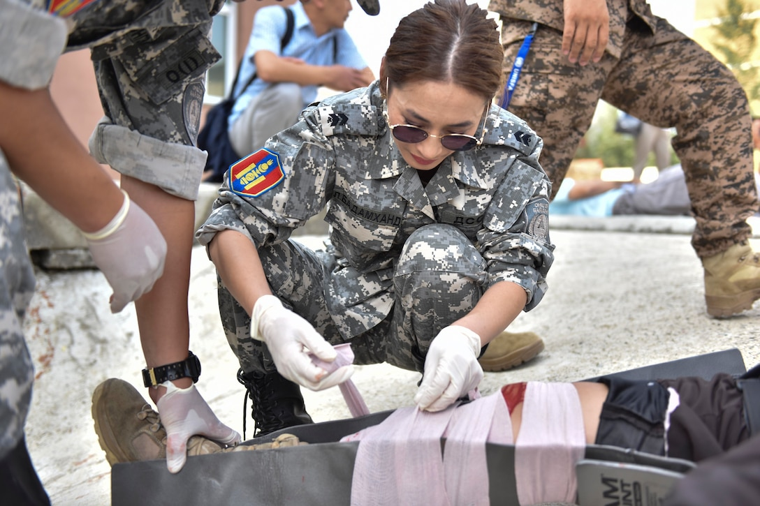 A Mongolian Armed Forces medic wraps a simulated leg wound Aug. 1, 2019, during Pacific Angel 19-3 in Ulaanbaatar, Mongolia. Efforts undertaken during PAC ANGEL help the U.S. and partner nations improve and build relationships across a wide spectrum of civic engagements, bolstering each nation's capacity to respond and support future humanitarian assistance and disaster relief operations. (U.S. Air Force photo by Senior Airman Eric M. Fisher)
