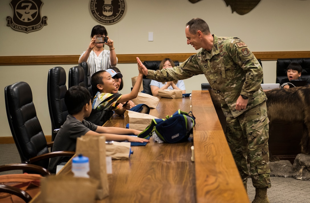 U.S. Air Force Col. Tad Clark, 8th Fighter Wing commander, high fives a local Korean child during a tour at Kunsan Air Base, Republic of Korea, Aug. 2, 2019. More than 20 children from the surrounding area were invited to tour the base and visit some of the facilities and organizations, such as the 8th Civil Engineer Squadron fire department. (U.S. Air Force photo by Senior Airman Stefan Alvarez)