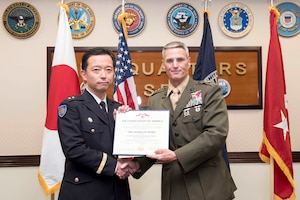 Japanese Ground Self-Defense Force Maj. Gen. Naoki Kajiwara, Director General, Defense Plans and Policy Department, Japan Joint Staff, is presented the Legion of Merit by U.S. Marine Corps Maj. Gen. Christopher Mahoney, Deputy Commander, Unites States Forces Japan, during a ceremony at Yokota Air Base, Japan, Aug. 8, 2019.