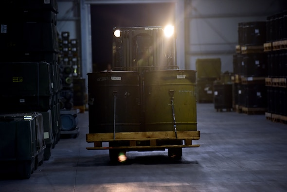 Barrels are transported by forklift in a warehouse during the night operations of Combat Ammunition Production Exercise 2019 on Aug. 7, 2019, at Aviano Air Base, Italy. Airmen are able to learn and enhance their skills during exercises allowing for improved combat readiness. (U.S. Air Force photo by Airman 1st Class Caleb House)