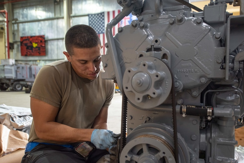 Staff Sgt. Adan Nunez, 380th Expeditionary Maintenance Squadron aerospace ground equipment craftsman, attaches an alternator to a four-cylinder diesel engine July 30, 3019, at Al Dhafra Air Base, United Arab Emirates. The engine provides power to a -86 generator which delivers 115 watts to the aircraft. (U.S. Air Force photo by Staff Sgt. Chris Thornbury)
