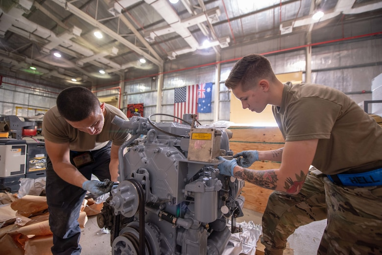Staff Sgt. Adan Nunez and Senior Airman Maeson Bella, 380th Expeditionary Maintenance Squadron aerospace ground equipment technicians, work on a diesel engine July 30, 3019, at Al Dhafra Air Base, United Arab Emirates. Removing the old engine, rebuilding and installing the new engine is a three-day process. (U.S. Air Force photo by Staff Sgt. Chris Thornbury)