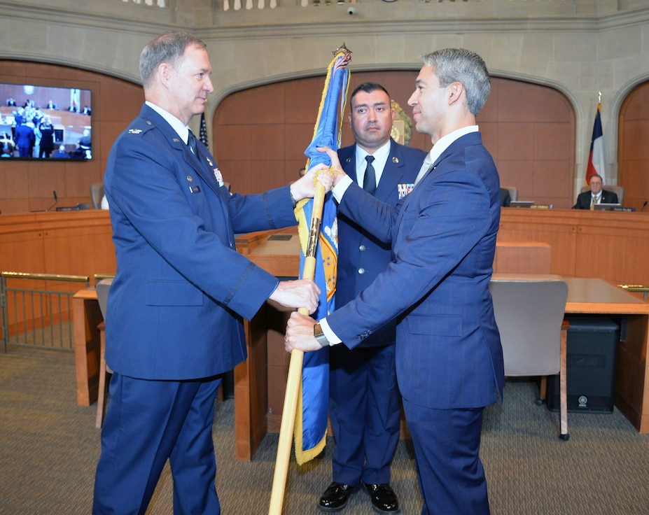 Col. Terry W. McClain, 433rd Airlift Wing commander, presents the wing guidon to San Antonio Mayor Ron Nirenberg during an honorary commander induction ceremony Aug. 8, 2019 in the city council chamber.