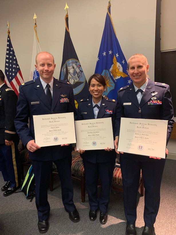 From left, U.S. Air Force Maj. Adam Hebdon, Maj. Cherielynne Gabriel, and Lt. Col. Kristen Soltis-Tyler  pose after receiving their Master in Public Health degrees from the Uniformed Services University of the Health Sciences in Bethesda, Maryland, June 20, 2019. The graduates will go on to be International Health Specialists at U.S. Air Force Air Component Commands. USUHS's MPH program offers a concentration in Global Health, equipping graduates with the skills they need as IHSs. (Courtesy photo)