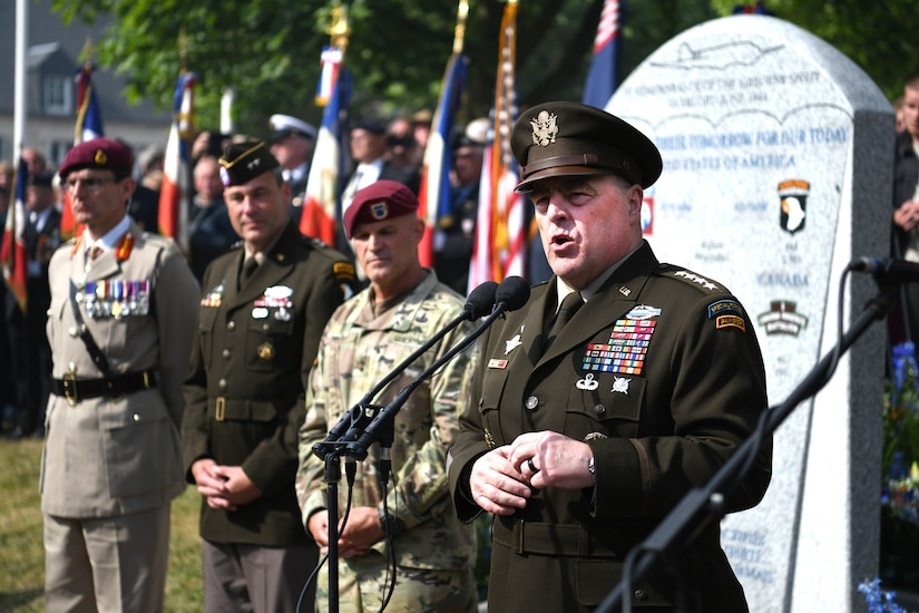 Soldier speaks in front of monument.