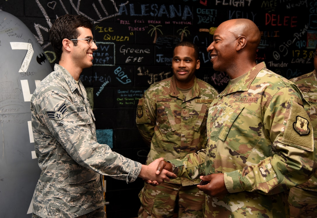 CMSAF presents a coin to a Senior Airman