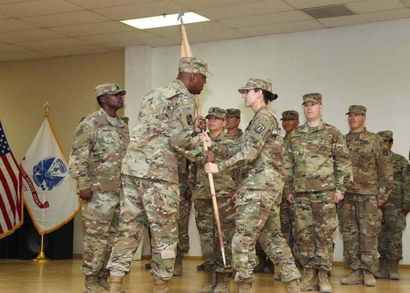 1st Lt. Caroline C. Shaw, outgoing commander Headquarters and Headquarters Company (HHC),, 335th Signal Command (Theater) (Provisional), passes the colors to Brig. Gen. Dion B. Moten, commanding general 335th SC (T)(P), during a combined Change of Command and Change of Responsibility Ceremony at Camp Arifjan, Kuwait, August 2, 2019. Capt. William A. Brinson and 1st Sgt. Yesenia S. Cooper formally accepted the command team reins of HHC, 335th SC (T) (P) from 1st Lt. Caroline C. Shaw and 1st Sgt. Shéshé A. Lang.
