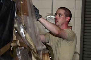 Senior Airman Matthew Ferhman, 87th Aerial Port Squadron air transportation journeyman, adjusts the top cargo net on a pallet in the cargo processing section at the 436th Aerial Port Squadron, Dover Air Force Base, Delaware, July 19, 2019 during his annual tour training