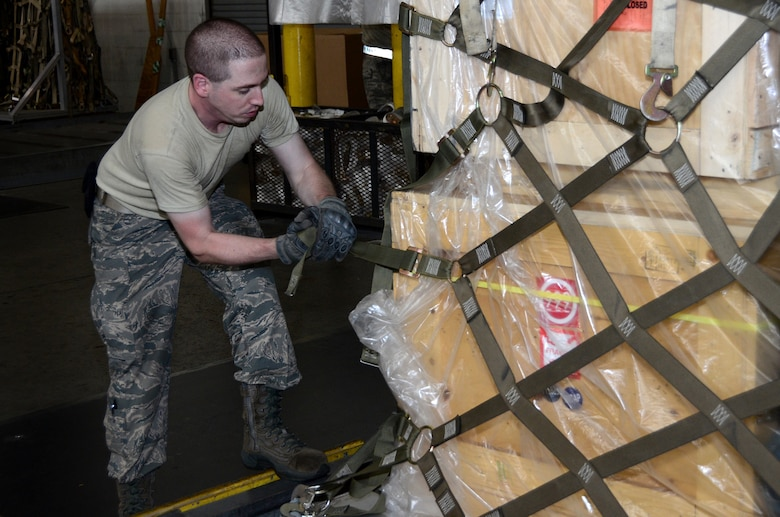 Senior Airman Matthew Ferhman, 87th Aerial Port Squadron air transportation journeyman, tightens a cargo net on a pallet in the cargo processing section at the 436th Aerial Port Squadron, Dover Air Force Base, Delaware, July 19, 2019 during his annual tour training