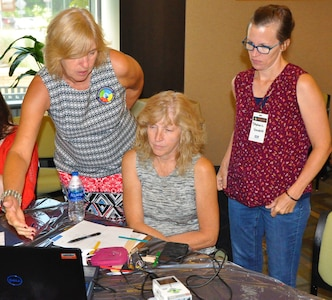 "IMAGE: KING GEORGE, Va. (July 30, 2019) – Navy engineer Page Wessel, left, briefs a local school teacher on the use of coding blocks to write a program for the Mindstorm EV3 robot at the Naval Surface Warfare Center Dahlgren Division (NSWCDD) STEM Workshop for Educators at the University of Mary Washington Dahlgren campus. Wessel was among the NSWCDD scientists and engineers who joined university professors at the workshop to share best practices and ideas for project based learning in STEM with elementary, middle, and high school educators. The forum featured briefings and demonstrations while the educators participated in hands-on activities that they could pass on to other teachers and students at their respective schools. The activities included, ""Straw Rockets and Mini-Railgun"", ""Ozobots and Littlebits Engineering"", and ""EV3 LEGO Robotics""."