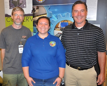 """IMAGE: KING GEORGE, Va. (July 30, 2019) – Navy human factors engineer Chelsey Lawson, middle, is pictured with her former high school teachers at the Naval Surface Warfare Center Dahlgren Division (NSWCDD) STEM Workshop for Educators at the University of Mary Washington Dahlgren campus. Lawson was among the NSWCDD scientists and engineers who joined university professors at the workshop to share best practices and ideas for project based learning in STEM with elementary, middle, and high school educators. Standing left to right at the workshop is Jeremy Webb from Spotsylvania High School; Lawson; and Jim McNamee from Commonwealth Governor's School.  """"Mr. Webb was my drafting teacher and Mr. McNamee was my math teacher for three years,"""" said Lawson. """"They were both very encouraging and influential not only in my high school education but also in choosing to be an engineer because they made STEM subjects interesting."""""""