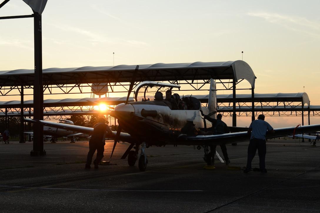 Student pilots sit in a T-6 Texan II while maintainers check the plane before takeoff on Aug. 5, 2019 at Columbus Air Force Base, Miss. Student pilots at Columbus will either be in the 37th Flying Training Squadron or the 41st Flying Training Squadron for a portion of their training. (U.S. Air Force photo by Airman Davis Donaldson)