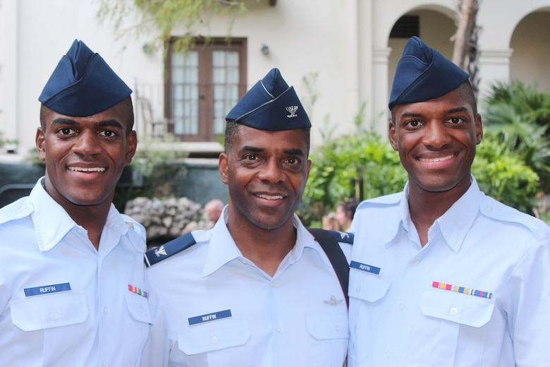 Airmen 1st Class Leernest Ruffin, left, and LeNard Ruffin, right, both 482nd Attack Squadron (ATK) intel analysts, and their father, Col. Leernest Ruffin, Headquarters United States Central Command deputy chief information officer, center, pose for a photo at basic military training (BMT) graduation at Joint Base San Antonio, Texas.