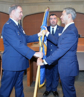 Col. Terry W. McClain, 433rd Airlift Wing commander, presents the wing guidon to San Antonio Mayor Ron Nirenberg during an honorary commander induction ceremony Aug. 8 at the San Antonio City Council chamber. The honorary commander program matches military commanders with local business and civic leaders to foster and grow understanding of the military mission and its impact on the surrounding community.