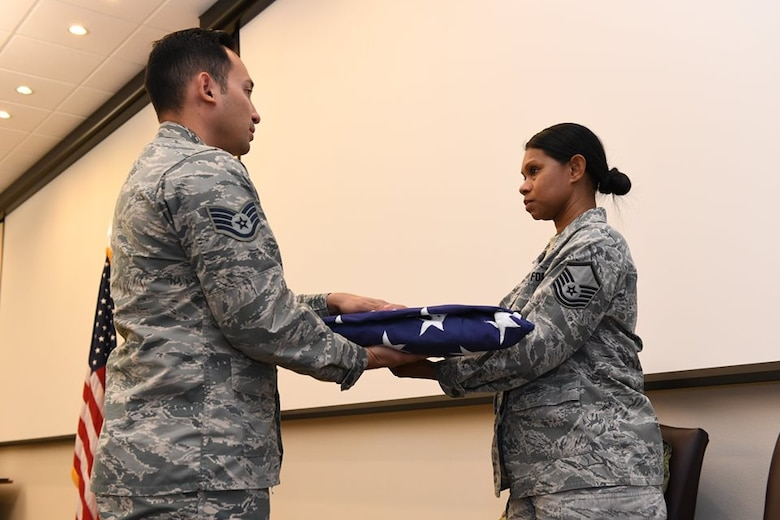 Master Sgt. Myra Heins, the 926th Wing Commander's Support Staff NCOIC, receives a flag from Staff Sgt. Joel Guerrero, a 926th Aerospace Medicine ceremonial team member, during her retirement ceremony Aug. 4 at Nellis Air Force Base, Nevada.