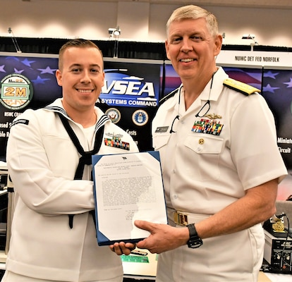Rear Adm. Lorin Selby, Naval Sea Systems Command Deputy Commander for Ship Design, Integration and Engineering  presents Southwest Regional Maintenance Center  Sailor, Petty Officer 2nd Class Adam T. Barber, with a Letter of Commendation for his work advancing the scope of the Navy and Marine Corps Miniature/Micro-miniature Module Test and Repair Gold Disk Program during the Fleet Maintenance and Modernization Symposium at the San Diego Convention Center on August 8.