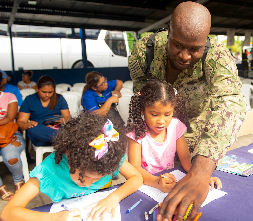 A man draws pictures with children.