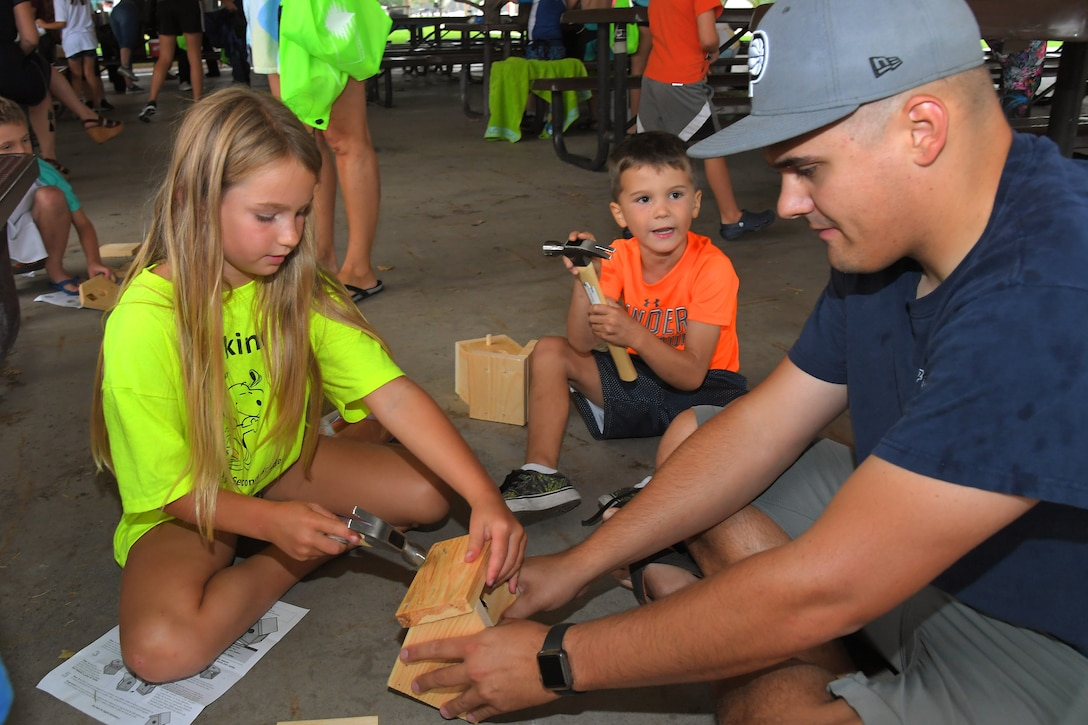 (Left to right) Paisley and Ricky build birdhouses with their father Tech. Sgt. Ricky Rea, 388th Aircraft Maintenance Squadron weapons load crew chief, during the Kickin' It for Conservation energy and environmental fair Aug. 8, 2019, at Hill Air Force Base, Utah. Although officially celebrated in April, the event served as the base's commemoration of Earth Day and was an opportunity for children and adults to learn how to conserve energy and protect the environment. (U.S. Air Force photo by Todd Cromar)