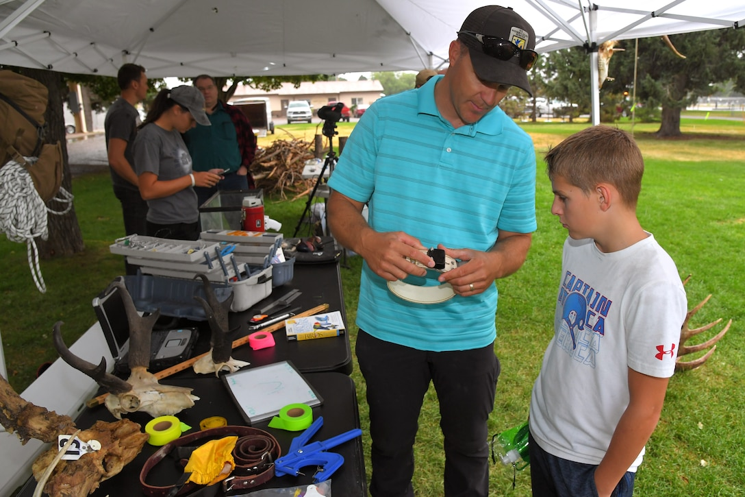 Nicholas Brown (left), U.S. Fish and Wildlife Service base liaison, explains wildlife tracking collars to Porter Lience during the Kickin' It for Conservation energy and environmental fair Aug. 8, 2019, at Hill Air Force Base, Utah. Although officially celebrated in April, the event served as the base's commemoration of Earth Day and was an opportunity for children and adults to learn how to conserve energy and protect the environment. (U.S. Air Force photo by Todd Cromar)