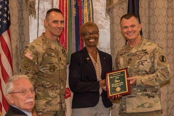 Gen. Paul E. Funk II, commanding general, U.S. Army Training and Doctrine Command, and TRADOC Command Sgt. Maj. Timothy A. Guden, pose for a photo with Dr. Evelyn Hollis, the 2019 Educator of the Year during the TRADOC Instructor of the Year Awards Ceremony at Fort Eustis, Va., Aug. 7, 2019. The seven awardees were recognized during a ceremony held at the TRADOC Commander's Forum.  (U.S. Army photo by Gwyndolynn Giacomo)