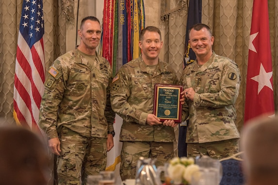 Gen. Paul E. Funk II, commanding general, U.S. Army Training and Doctrine Command, and TRADOC Command Sgt. Maj. Timothy A. Guden, pose for a photo with Capt. Matthew Weather, the 2019 Active Duty Instructor of the Year during the TRADOC Instructor of the Year Awards Ceremony at Fort Eustis, Va., Aug. 7, 2019. The seven awardees were recognized at a ceremony held during the TRADOC Commander's Forum. (U.S. Army photo by Gwyndolynn Giacomo)