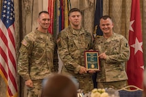 Gen. Paul E. Funk II, commanding general, U.S. Army Training and Doctrine Command, and TRADOC Command Sgt. Maj. Timothy A. Guden, pose for a photo with Sergeant 1st Class Clifford Hammond III, the 2019 Active Duty Noncommissioned Officer Instructor of the Year during the TRADOC Instructor of the Year Awards Ceremony at Fort Eustis, Va., Aug. 7, 2019. The seven awardees were recognized at a ceremony during the TRADOC Commander's Forum.  (U.S. Army photo by Gwyndolynn Giacomo)
