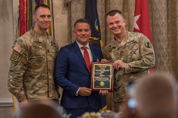 Gen. Paul E. Funk II, commanding general, U.S. Army Training and Doctrine Command, and TRADOC Command Sgt. Maj. Timothy A. Guden, pose for a photo with Ryan Klagenberg, the 2019 Reserve Instructor of the Year during the TRADOC Instructor of the Year Awards Ceremony, at Fort Eustis, Va., Aug. 7, 2019. The seven awardees were recognized at a ceremony during the TRADOC Commander's Forum.  (U.S. Army photo by Gwyndolynn Giacomo)